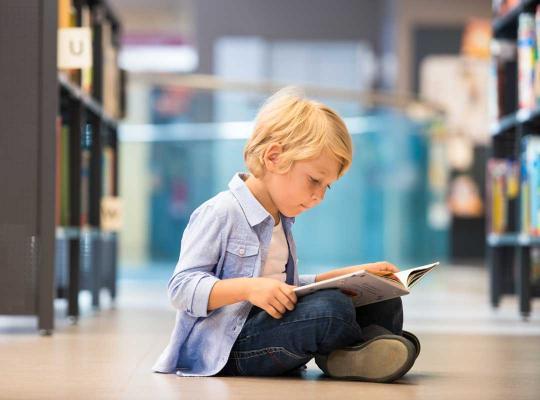 Kind leest boek in bib
